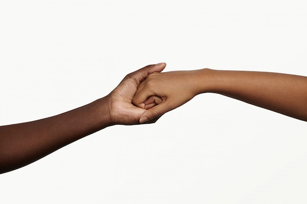 Two african people holding their hands tight together. Free Photo