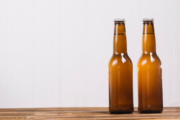 Two alcoholic bottles on wooden desk Free Photo