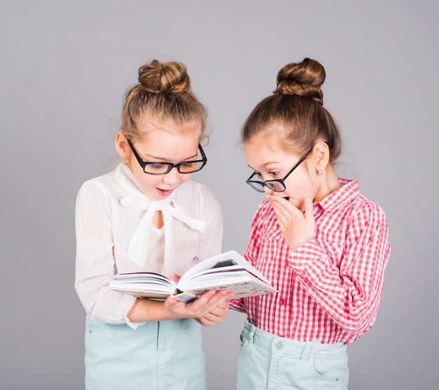 Two amazed girls in glasses reading book Free Photo