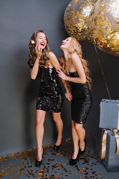 파티를 축하하는 럭셔리 블랙 드레스에 두 놀라운 재미 젊은 여성. 긴 곱슬 머리, 매력적인 외모, 붉은 입술, 쾌활한 분위기, 웃음, 재미, 생일 축하 파티. 무료 사진