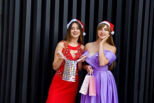 サンタの帽子と買い物袋を持っているエレガントなイブニングドレスの2人の素晴らしい女性 Premium写真
