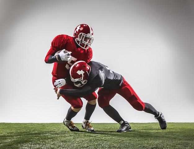 I due giocatori di football americano in azione su erba verde e sfondo grigio. Foto Gratuite