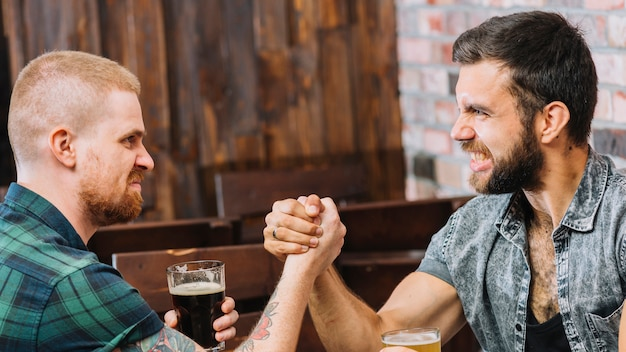 Two angry men arm wrestling Free Photo