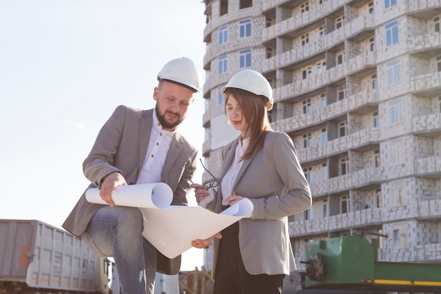 Two architects holding blueprint and discussing project while working together Free Photo