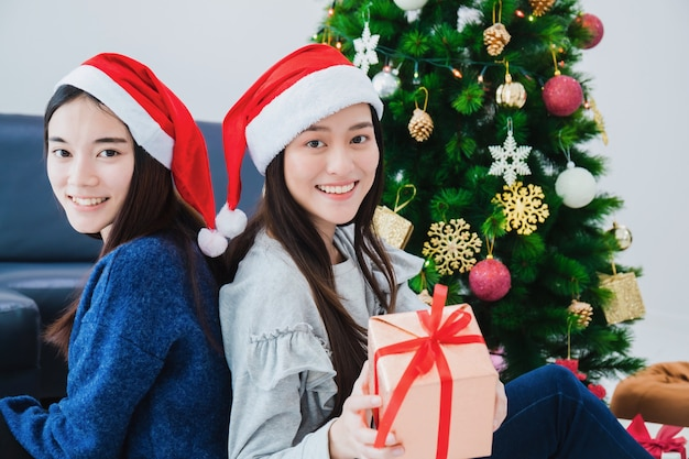 Two asian beautiful woman holding gift boxes. smiling face in room with christmas tree decoration for holiday Premium Photo