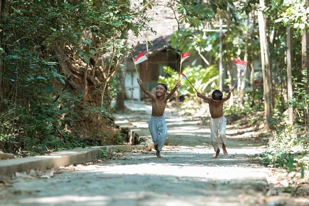 Два азиатских мальчика бегают без одежды, гоняясь друг за другом, держа в руках красно-белый флаг Premium Фотографии