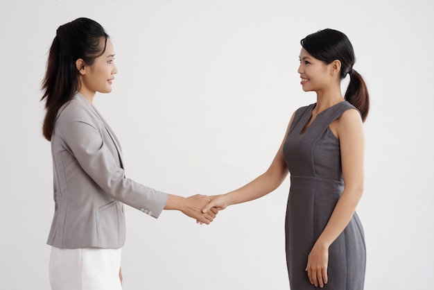 Two asian business women standing indoors, shaking hands and smiling Free Photo