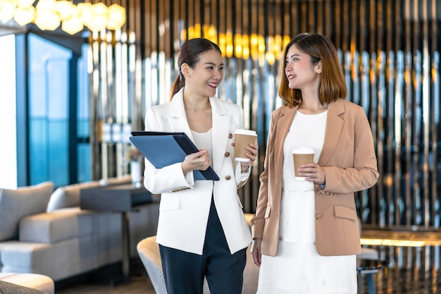 Two asian businesswomen talking during coffee break in modern ...