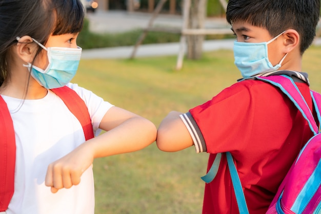 Two asian children preschool friends meet in  school park instead of greeting with a hug or handshake, they bump elbows instead. Premium Photo