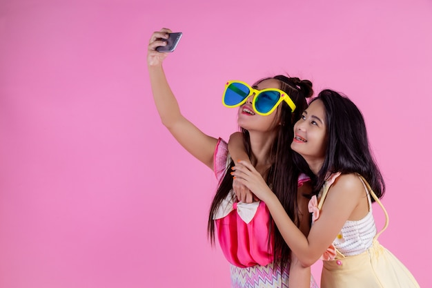 Two asian girls who are friends are happy and have a pink . Free Photo