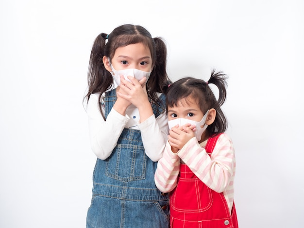 Two asian little cute girl sibling wearing a hygienic mask and covering they mouth with her hand to protection spread the virus, cold flu or pollution. Premium Photo