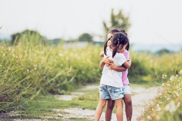 Two asian little girls hugging each other with love in vintage color tone Premium Photo