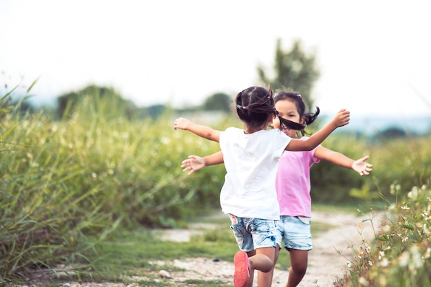 Two asian little girls running to give a hug each other in vintage color tone Premium Photo