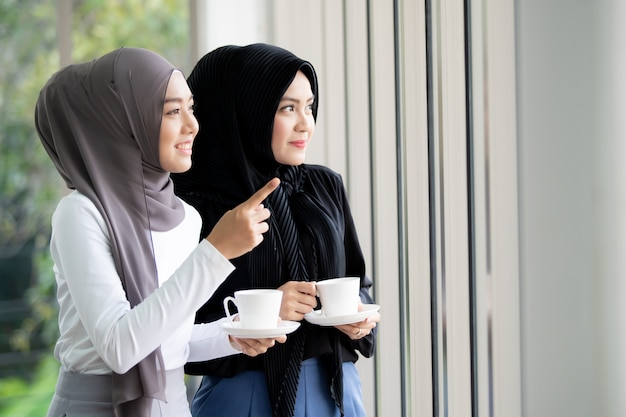 Two asian muslim woman standing and talking in the office with a cup of coffee. modern muslim lifestyle concept. Premium Photo