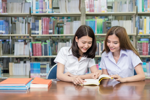 Two asian students studying together in library at university. Premium Photo