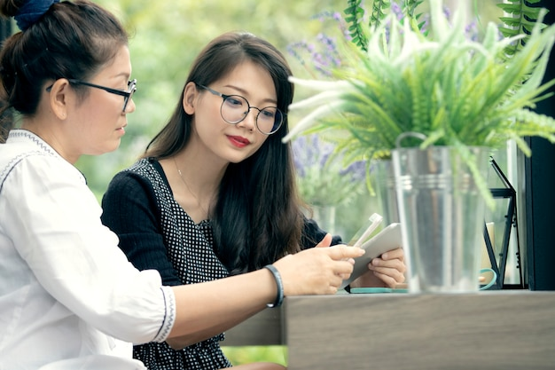 Two asian woman with phone in hand talking  in home living room with happiness face Premium Photo