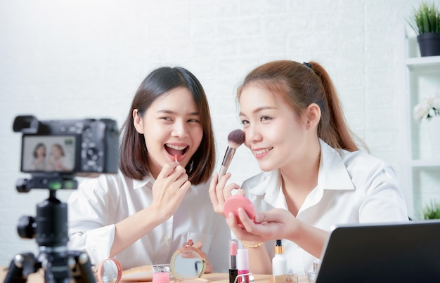 Two asian women beauty vlogger video online is showing make up on cosmetics products and live video Premium Photo