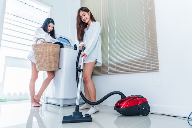 Two asian women doing housework and chores in kitchen Premium Photo