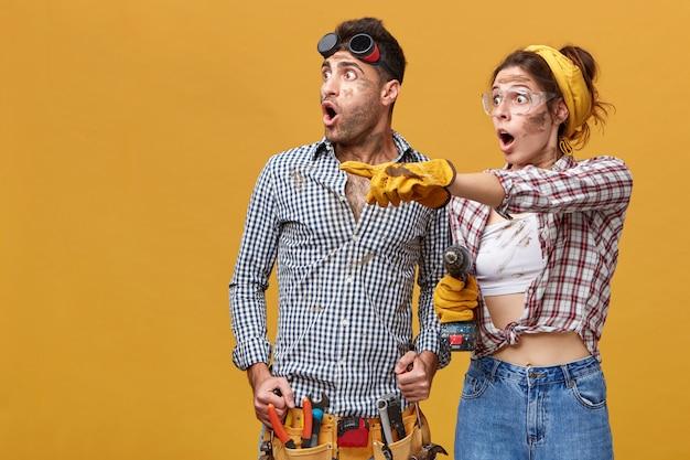 Два изумленных электрика с грязными лицами в шоке искоса смотрят в сторону: женщина в защитных перчатках и очках указывает на что-то пальцем. риск, высокое напряжение, сопротивление и опасности на работе Бесплатные Фотографии