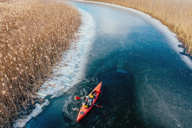 Two athletic man floats on a red boat in river Free Photo