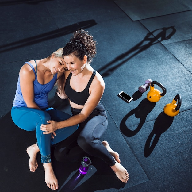 Two athletic smiling women sitting together in gym Free Photo