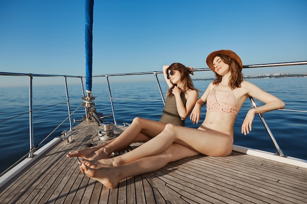 Two attractive adult woman on yacht, sailing in sea and sunbathing on bow of boat, feeling relaxed and pleased. hot women want get tan so they changed in bikinis. summertime happiness Free Photo