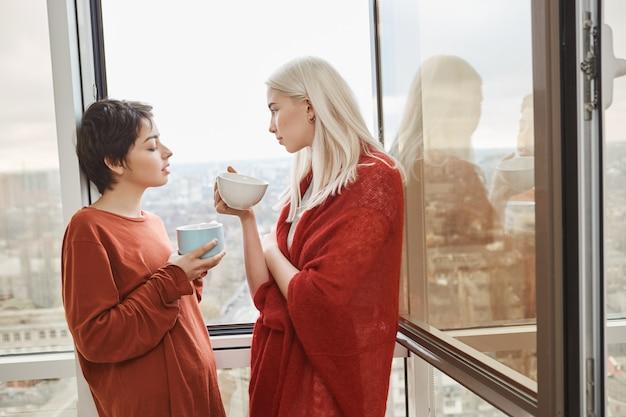 Две привлекательные и чувственные подруги стоят возле открытого окна в красной одежде, попивая кофе Бесплатные Фотографии