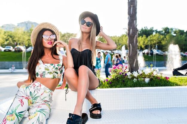 Due ragazze bionde e castane attraenti con capelli lunghi stanno proponendo alla macchina fotografica nel parco. indossano abiti sexy, cappello e occhiali da sole. Foto Gratuite