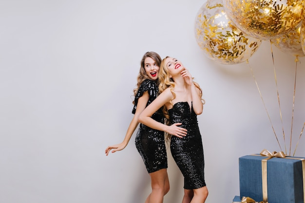 Two attractive fashionable young women in luxury black dresses celebrating party. having fun, elegant look, smiling, true emotions. big present, golden balloons, tinsels. Free Photo