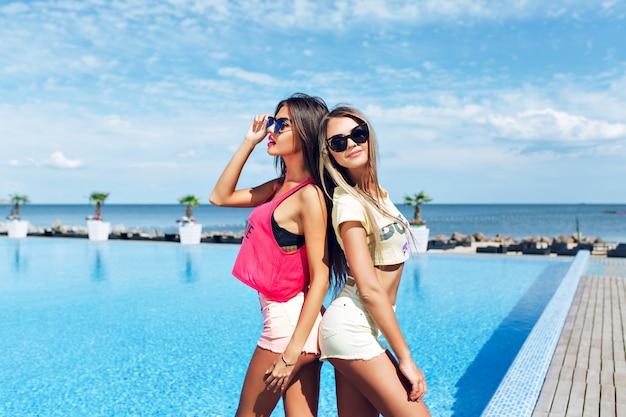 長い髪の2人の魅力的な女の子が太陽の下でプールの近くでポーズをとっています。彼らは背中合わせに立っています。 無料写真