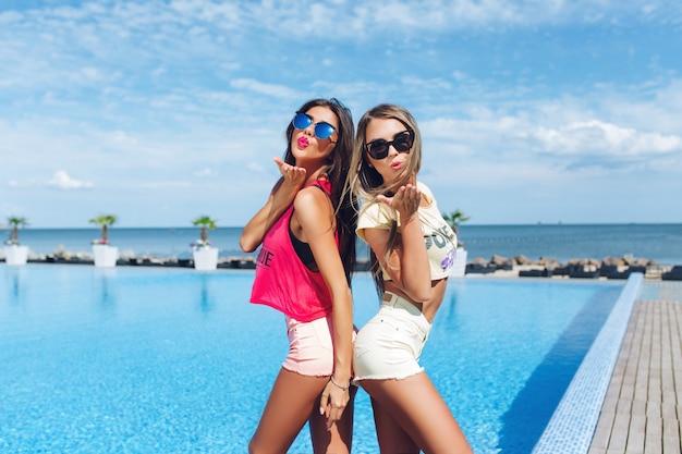 サングラスの長い髪を持つ2人の魅力的な女の子が太陽の下でプールの近くでポーズをとっています。彼らは背中合わせに立っています。 無料写真