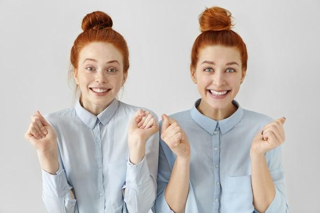 Две привлекательные счастливые молодые рыжие женщины с узлами волос в голубых рубашках Бесплатные Фотографии