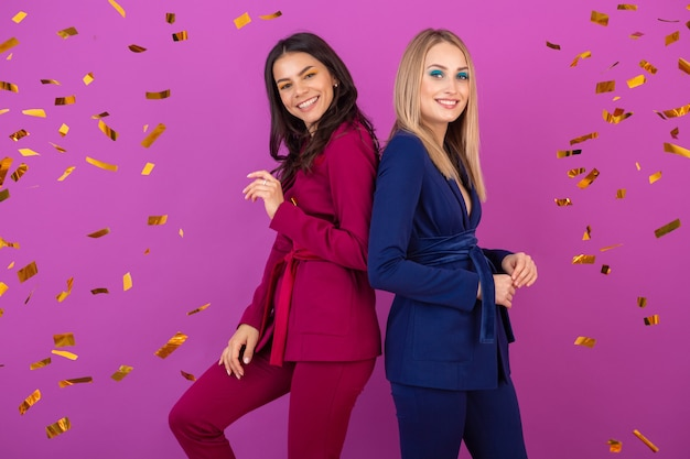 Two attractive women celebrating new year on violet wall in stylish colorful evening suits of purple and blue color, friends having fun together, fashion trend, golden confetti party mood Free Photo