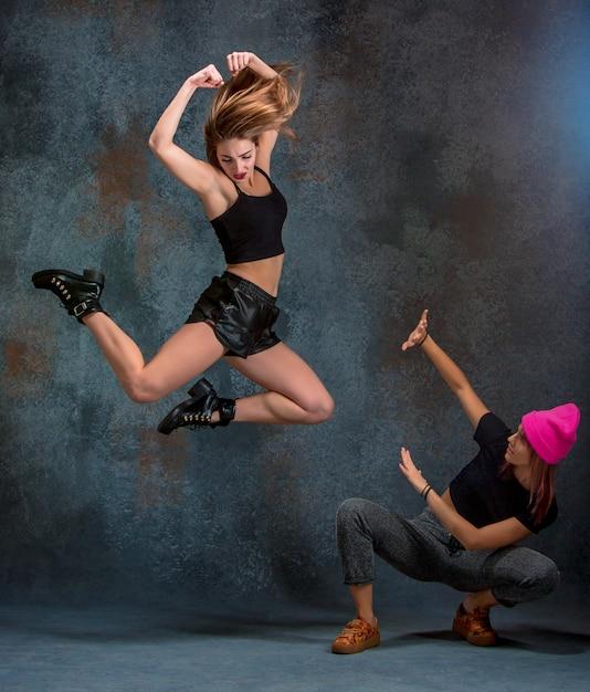 The two attractive women dancing twerk in the studio Free Photo