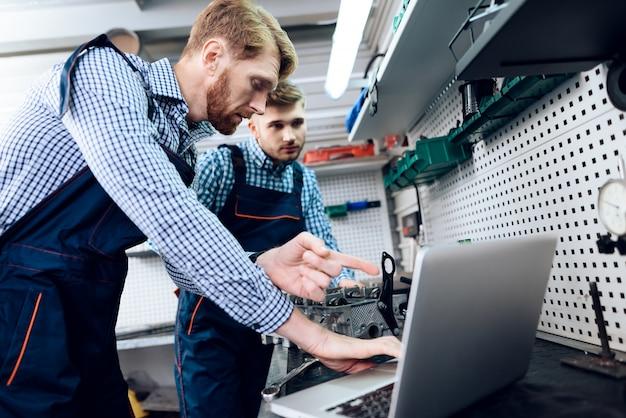 Two auto mechanics work together in garage. Premium Photo