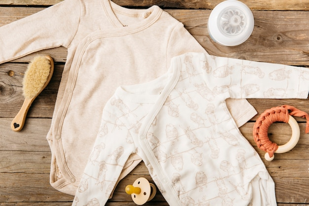 Two baby onesie; brush; milk bottle; toy and pacifier on wooden table Free Photo