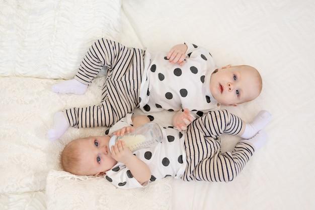 2人の赤ちゃん双子の兄と妹はパジャマ姿でベッドに横になり、ボトル、ベビーフードのコンセプト、上面から牛乳を飲む Premium写真