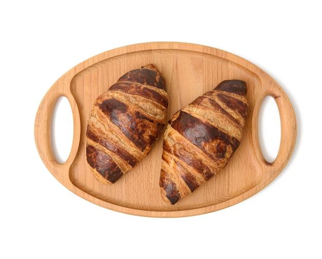 Два запеченных круассана лежат на деревянном подносе, еда изолирована на белом фоне, вид сверху Premium Фотографии