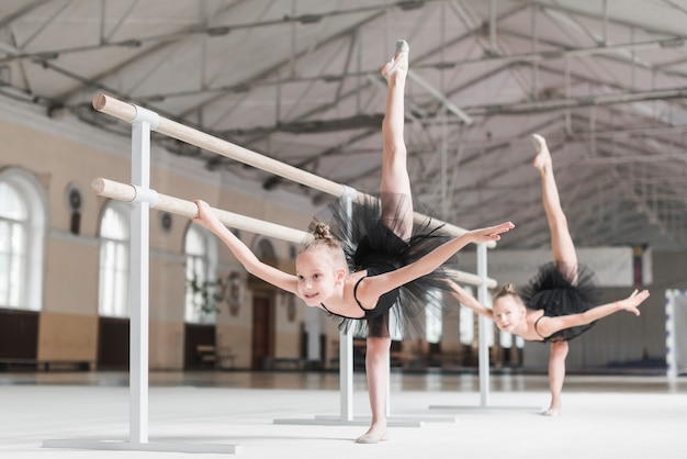 Two ballerina girls stretching their legs up with barre support in dance class Free Photo