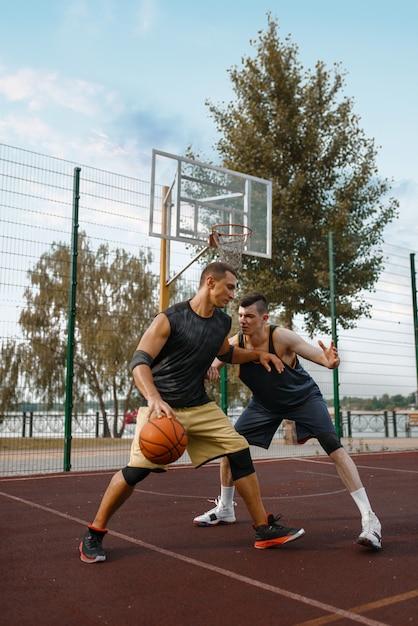Два баскетболиста устроили матч на открытой площадке, активный отдых. Premium Фотографии