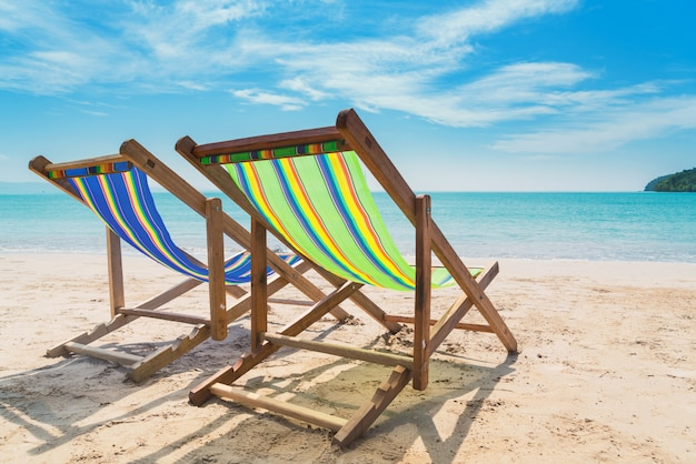 Two beach chairs on the white sand with blue sky and summer sea background. Premium Photo