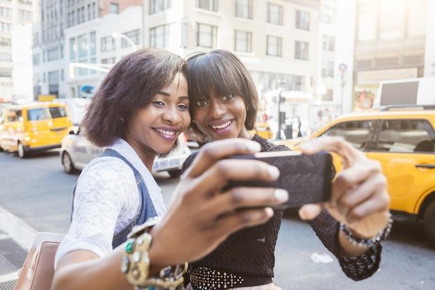 Two beautiful black woman taking selfie in new york Premium Photo