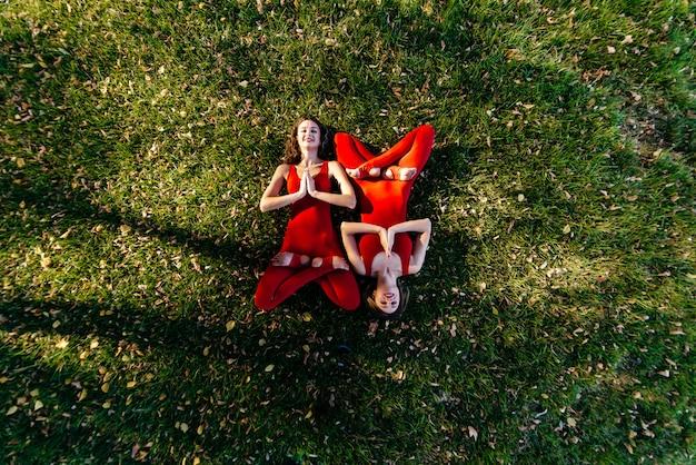Две красивые брюнетки женщины носят тесную активную одежду, выполняя позы йоги в парке на фиолетовые коврики с мягкими вспышками солнца сквозь деревья Premium Фотографии