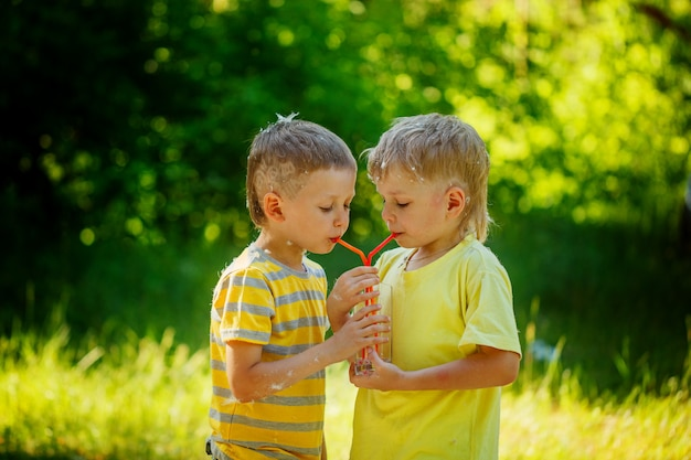 Two beautiful children, boy friends,  drinking water in the park Premium Photo