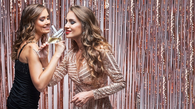 Two beautiful elegant women in evening dresses drinking champagne. Premium Photo