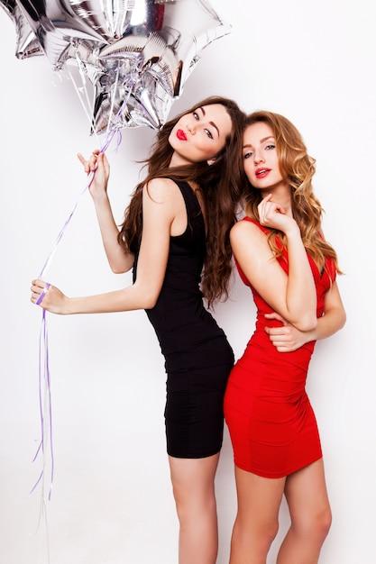 저녁 검정과 빨강 드레스 재미에 붉은 입술으로 두 아름 다운 우아한 여성. 하나는 그녀의 손에 은색 별 풍선을 유지하고 웃고. 무료 사진