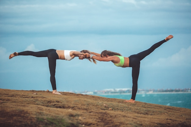 Two beautiful girl doing yoga Free Photo