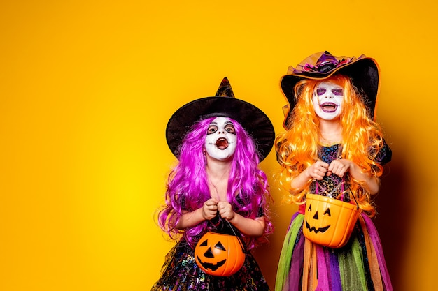 Two beautiful girl in a witch costume scaring and making faces Premium Photo
