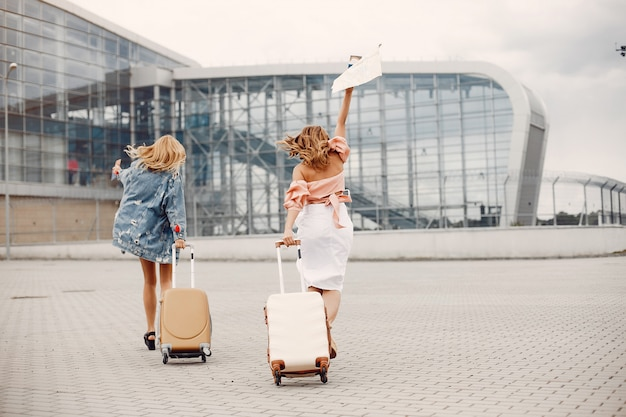 Two beautiful girls standing by the airport Free Photo