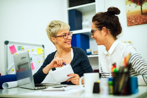 2人の美しい中年女性の同僚が一緒に働いて、オフィスの机に座ってお互いを見ています。 Premium写真